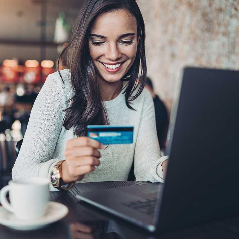 A woman using a laptop to make a payment using her credit card